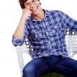 Smiling guy on chair with hand under cheek — 图库照片