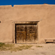 Adobe building with old door and bench — Stock Photo #22599265