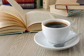 Cup of coffee on a table with books — Stock Photo