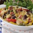 Stock Photo: Beans with ham and vegetables, baked with cheese
