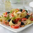 Pasta salad with ham, tomato and olives - Stock Photo