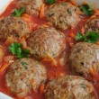 Meatballs with herbs and tomato sauce in the pan - Stock Photo