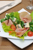 Appetizer with slices of jamon and blue cheese with cherry — Stock Photo