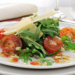 Salad of arugula and cherry tomatoes with parmesan sauce — Stock Photo