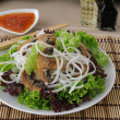 Rice noodles with mushrooms in breadcrumbs in lettuce leaves — Stock Photo