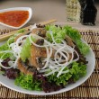 Rice noodles with mushrooms in breadcrumbs in lettuce leaves — Stock Photo #24889217