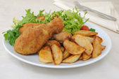Chicken drumsticks with breadcrumbs with potatoes and salad — Stock Photo