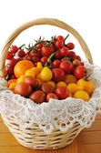 Different varieties of tomatoes in a basket — Stock Photo