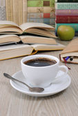 A cup of coffee on a table among books — Stock Photo