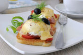 Eggs Benedict with ham and tomato on toast with cheese — Stock Photo