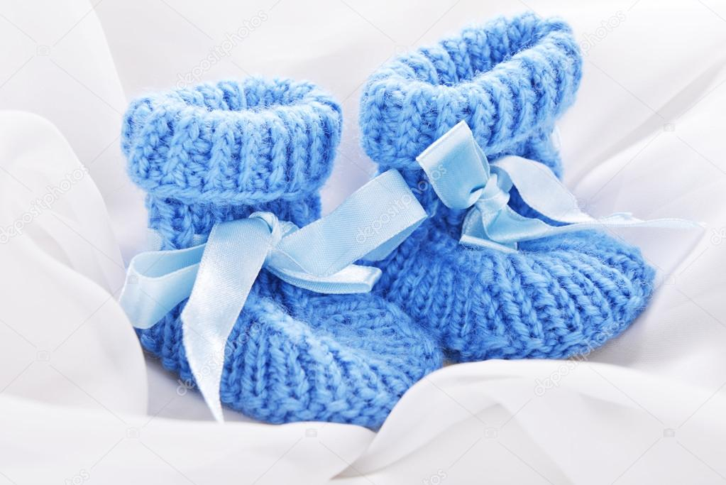 Handmade  baby booties isolated on a white silk background — Stock Photo #14451325