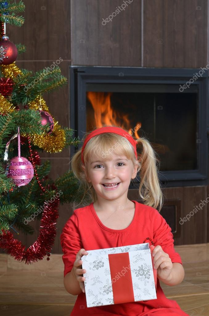 Pretty little girl  with gift near Cristmas tree  Stock Photo #16285073