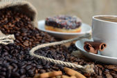 Cup of coffee and dark brown roasted coffee beans — Stock Photo