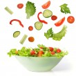 Vegetables falling into a bowl of salad — Stock Photo