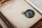 Compass and watch on old book — Stock Photo