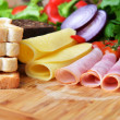 Meat, cheese, bread and vegetables — Stock Photo
