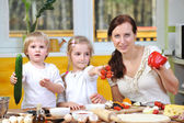 Mother with children cut vegetables for pizzas — Stock Photo