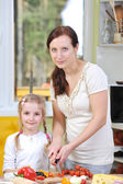 Mother with daughter cut vegetables for pizzas — Stock Photo