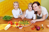 Mother with children preparing to eat fresh pizza — Stock Photo