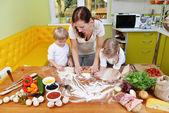 Mother with children on kitchen — Stock Photo