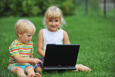 Little girl with brother with laptop — Stock Photo