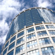 Modern office round tower building over sky with clouds — Stock Photo #12216595