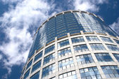 Modern office round tower building over sky with clouds — Stock Photo