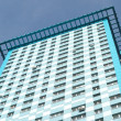 Bottom view of high modern apartment building on clear blue sky — Stock Photo