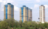 City landscape with high modern apartment buildings on blue sky with clouds — Stock Photo