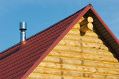 Top of country wooden house with red roof and metal smokestack — Stock Photo
