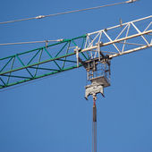 Green and white construction hoisting crane part over clear cloudless blue sky — Stock Photo