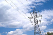 Metal prop and high-voltage power line over blue sky with white clouds — Stock Photo
