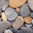 Many smooth sea stones on a beach closeup — Stockfoto