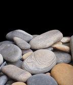 Mnoho hladké moře kameny izolovaných na černé closeup — Stock fotografie