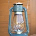 Retro oil kerosene lantern over country house part closeup — Stock Photo