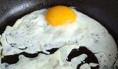 Fried egg in black pan closeup — Stock Photo