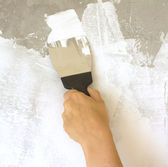 Woman's hand with a spatula plasters wall — Stock Photo