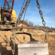 Big heavy excavator bucket and mountain of sand in autumn — Stock fotografie