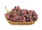 Red grape on branch in straw wicker basket isolated — Stock Photo