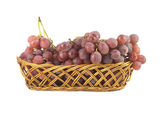 Red grape on branch in straw wicker basket isolated — 图库照片