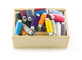 Colored spools with thread in wooden box isolated close up — Stock Photo