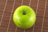 Ripe apple on brown wicker straw mat close up — Stock Photo