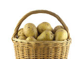 Potatoes in brown wicker basket isolated closeup — Stock Photo