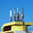 Stock Photo: Many electronics aerials on yellow building top