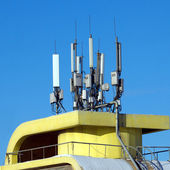 Many electronics aerials on yellow building top — Stock Photo