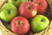 Ripe color apples in brown wicker basket isolated — Stock Photo