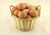 Chicken eggs in wicker basket on beige cloth isolated — Stock Photo