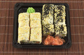 Sushi rolls in plastic container on wicker straw mat closeup — Stock Photo