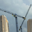 Big hoisting tower cranes and constructed buildings — Stock Photo