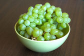 Grape on branch in green bowl close up — Stock Photo